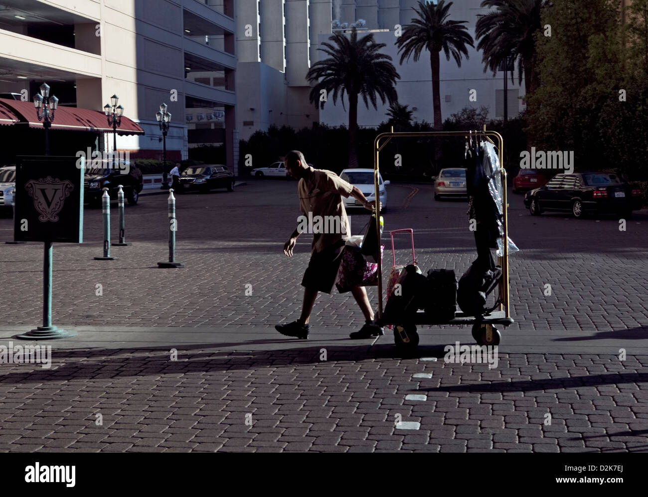A BELLHOP PULLS  A LUGGAGE TROLLEY INTO HOTEL IN LAS VEGAS, OCT 2010 - Stock Image