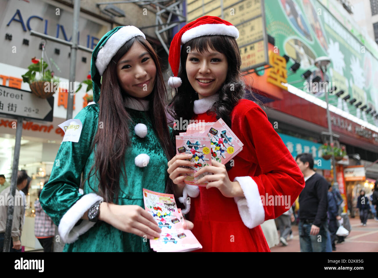 Hong Kong, China, disguised as Weihnachsmaenner Asian distribute promotional flyers - Stock Image