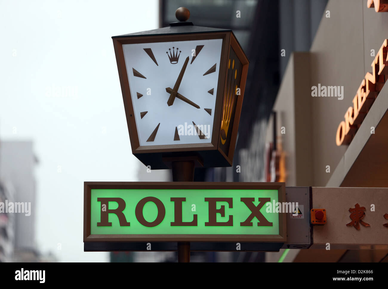 Hong Kong, China, Rolex clock and lettering from a drainpipe - Stock Image