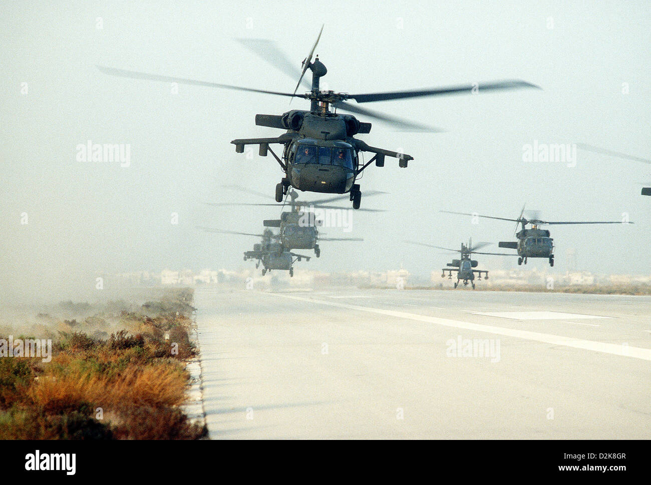 US Army UH-60A Blackhawk helicopters and one AH-64A Apache helicopter, second from right conduct a mass takeoff - Stock Image