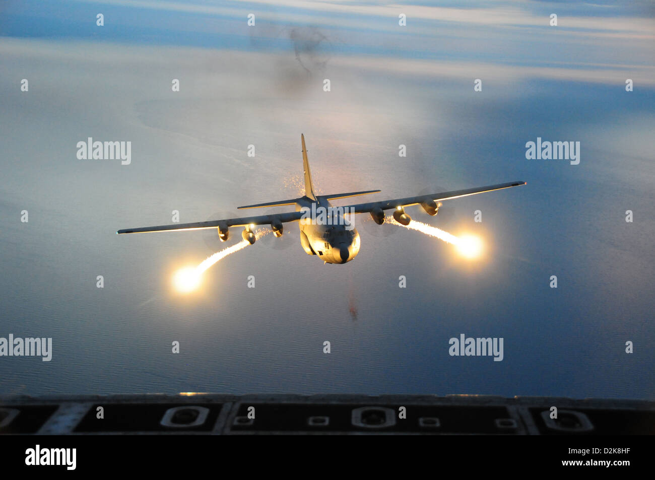 A C-130 night training mission uses live flares as an aerial infrared countermeasure used to defeat infrared homing - Stock Image