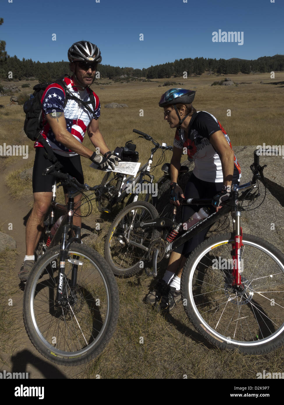 Two mountain bikers stopped and one needing a rest Mount Laguna california - Stock Image