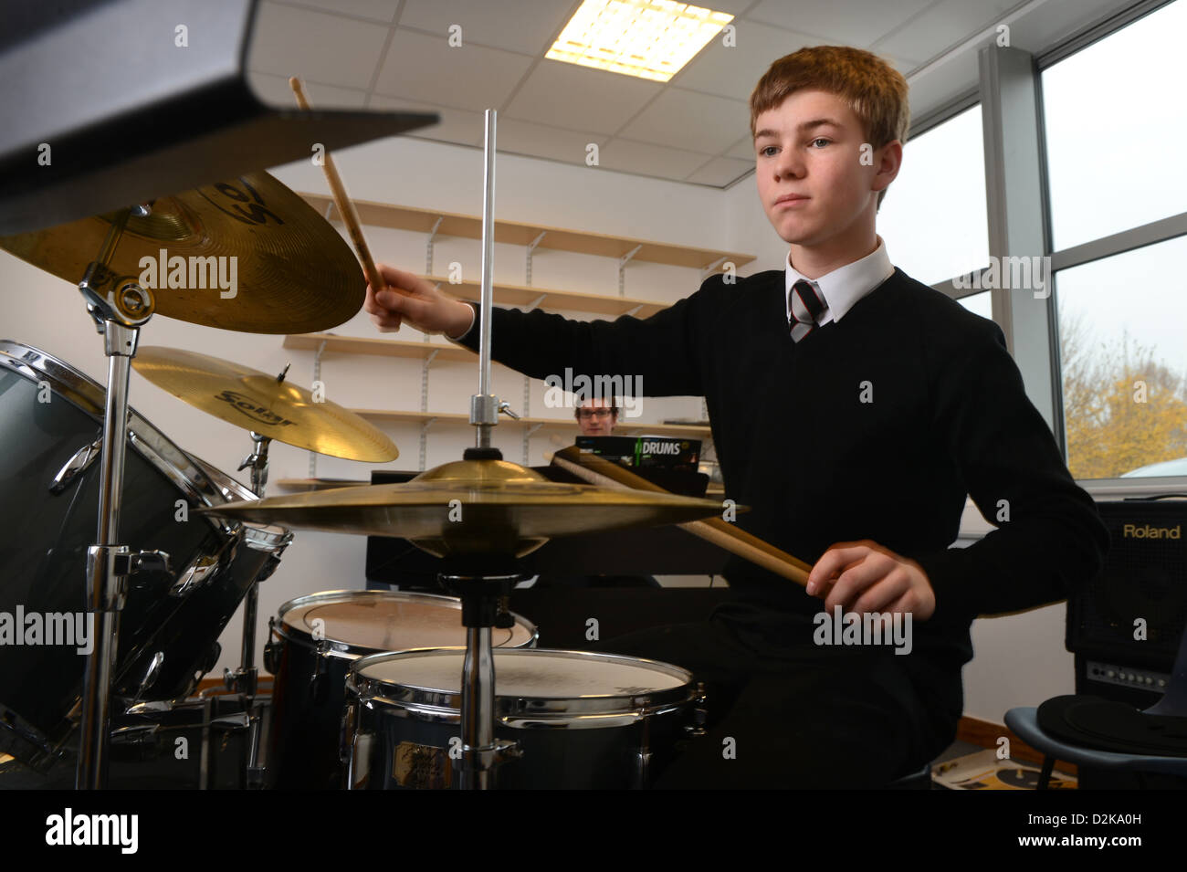 A school boy drumming in a music lesson at Pates Grammar School in Cheltenham, Gloucestershire UK - Stock Image