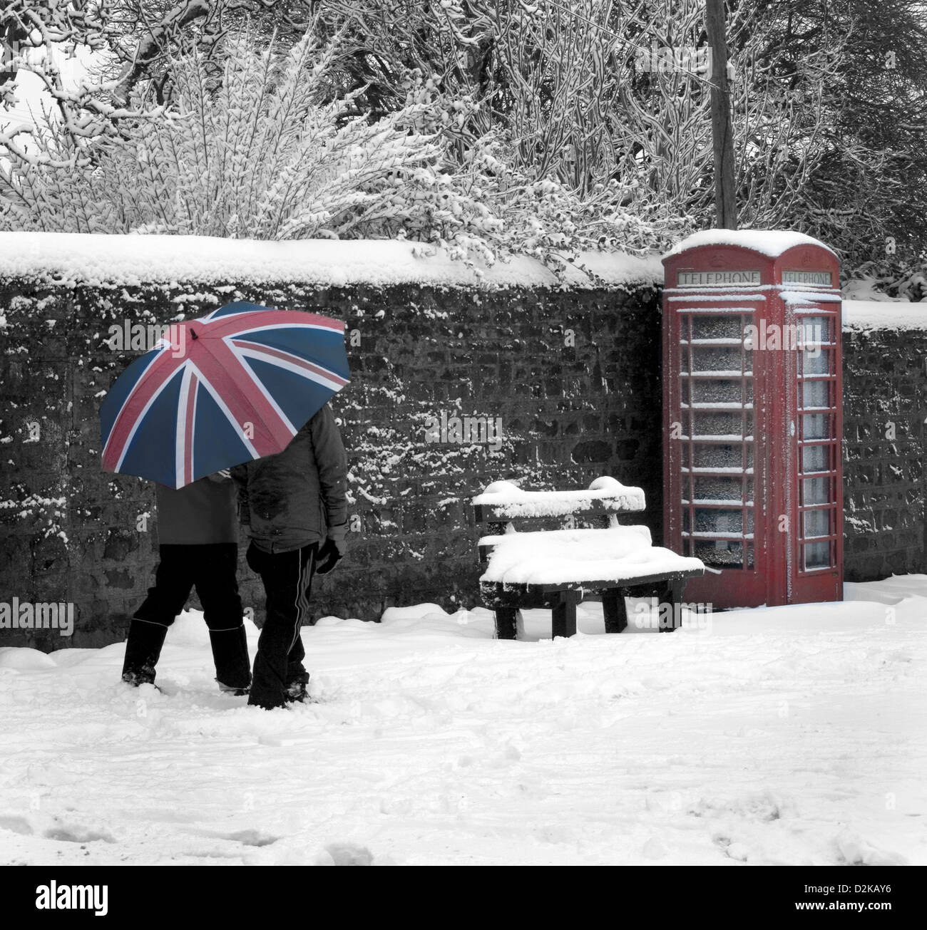Uk , British, Red Telephone box with snow and union jack umberella. Scenic view of a British winter.Black and white - Stock Image