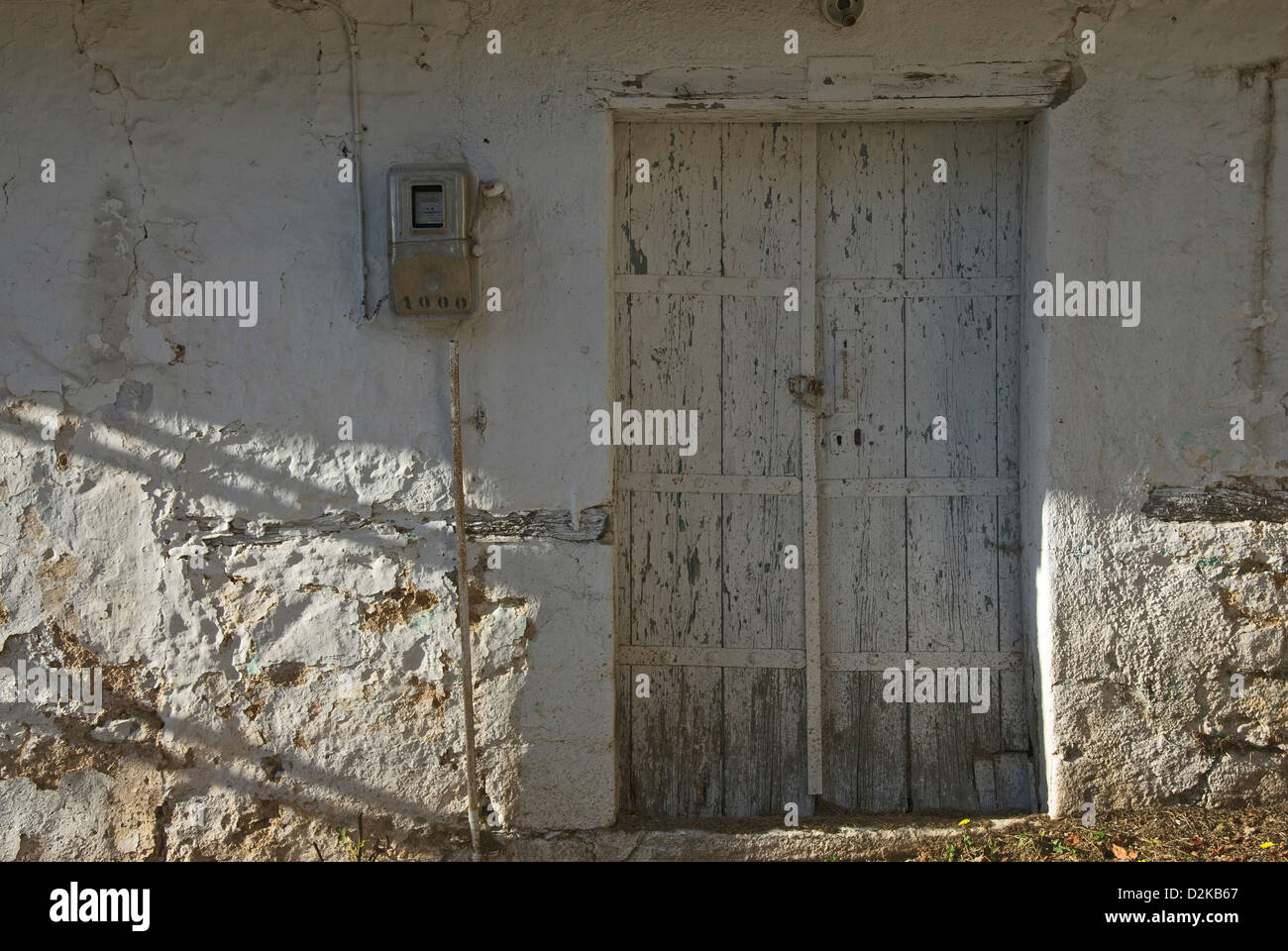 Old front door in weathered house front (Greece) - Stock Image
