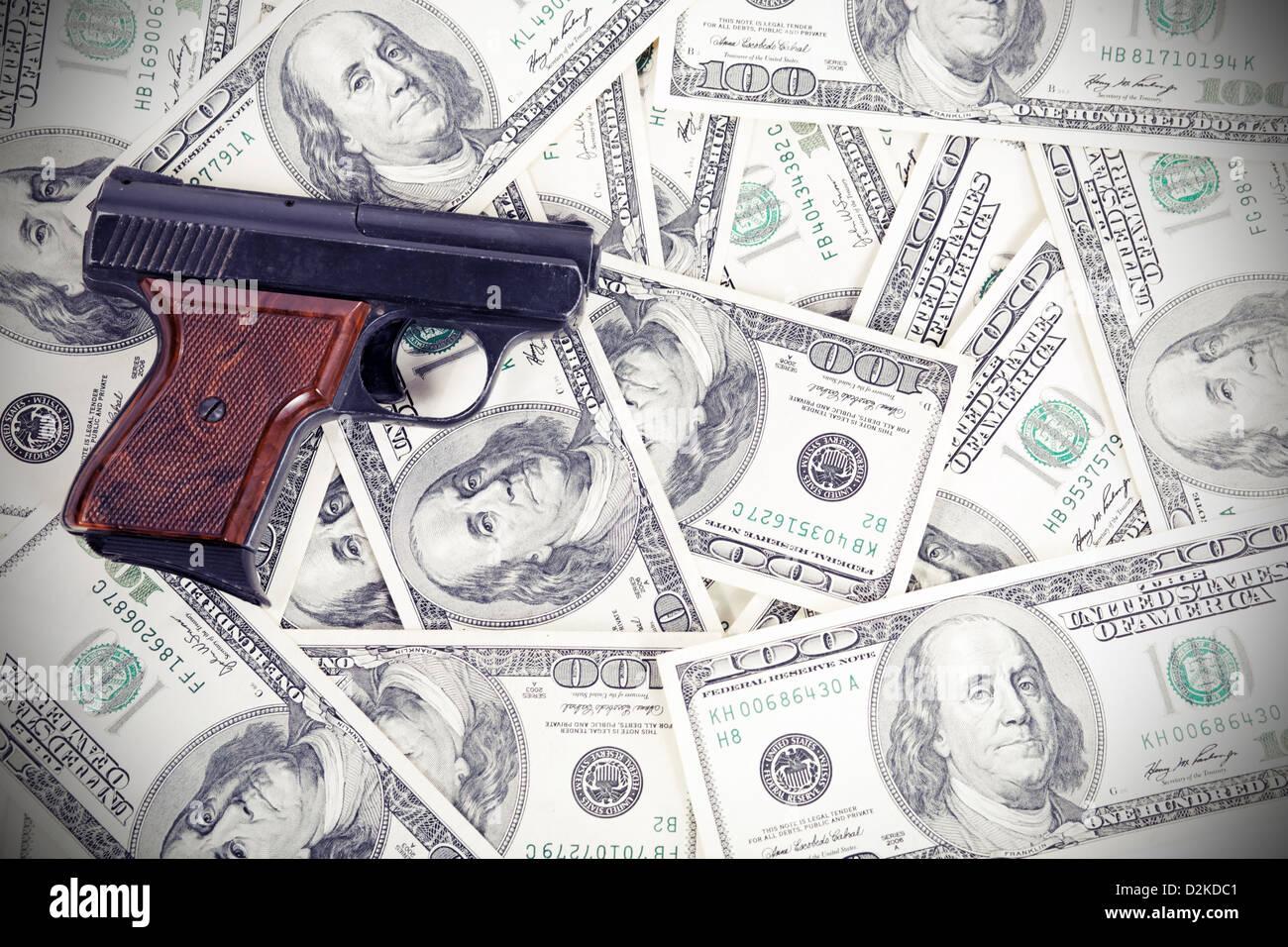 a gun lying on the criminal-earned money - Stock Image