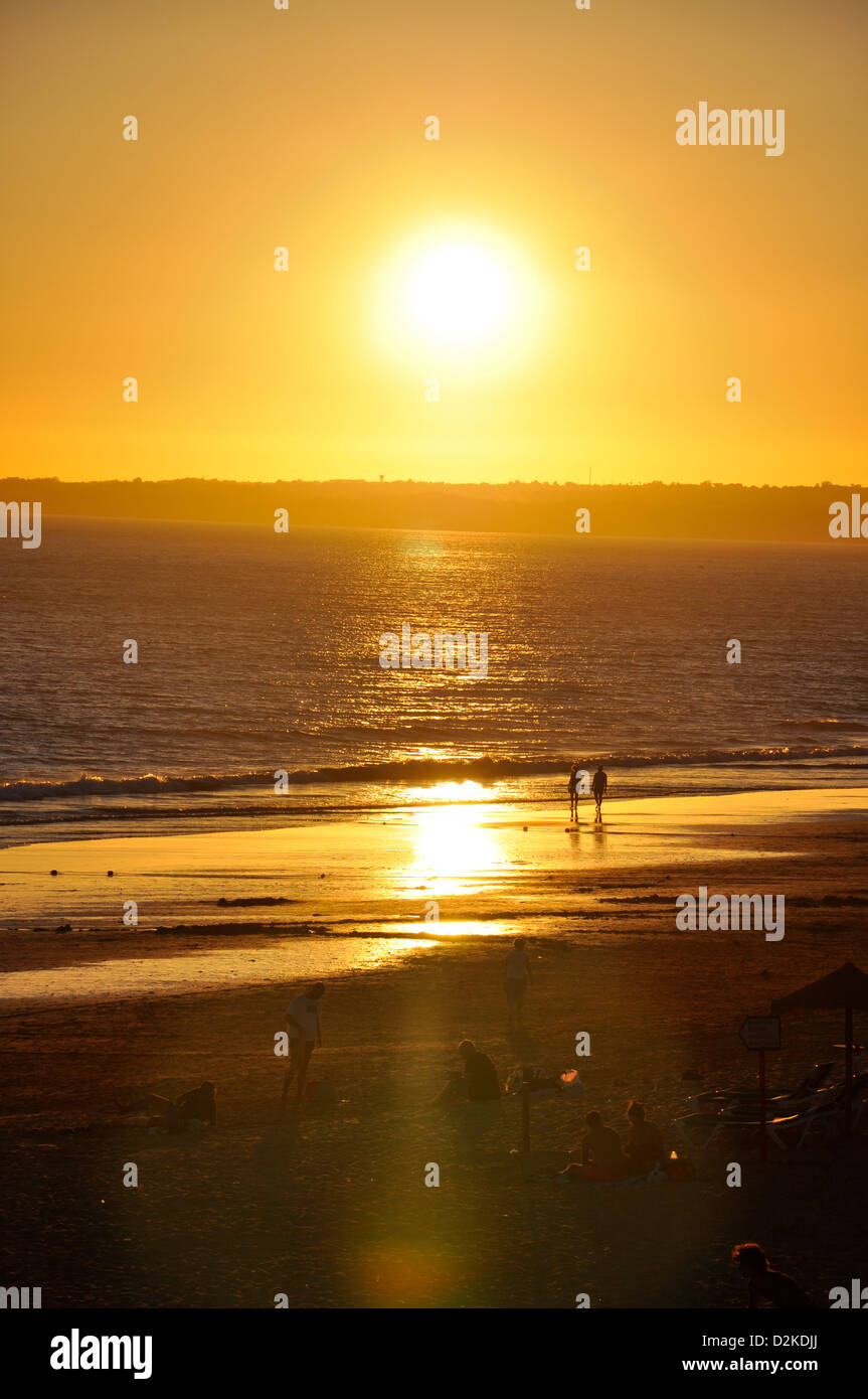 Couple walking in on beach at sunset in Gale, Faro District, Algarve Region, Portugal - Stock Image