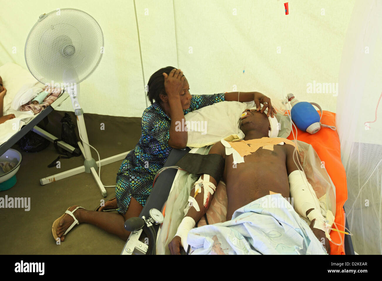 Carrefour, Haiti, a kneeling beside a wounded relatives in the intensive care unit - Stock Image