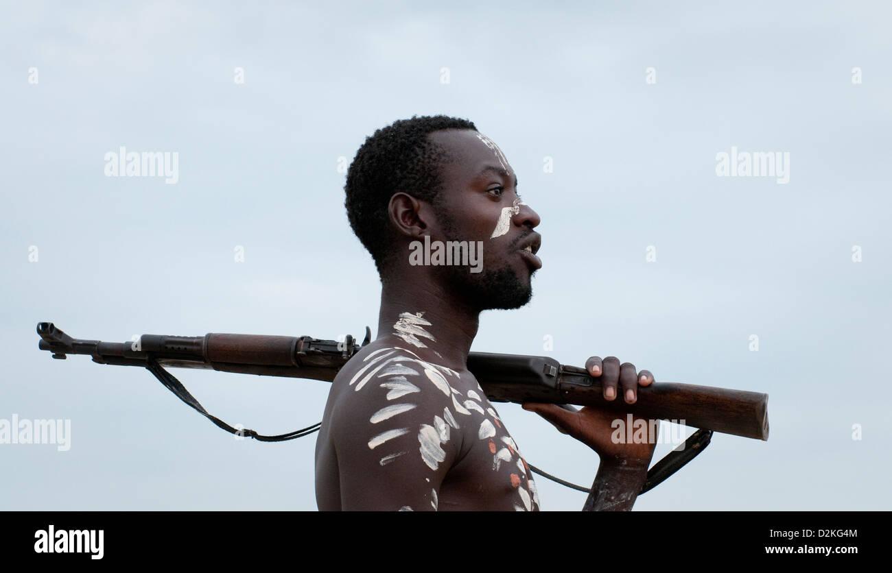 Portrait of decorated Kara man,holding rifle-close up - Stock Image