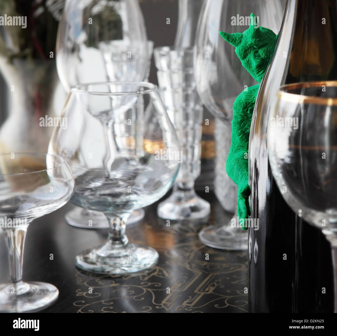 a little green devil peeks out from behind a bottle of wine. A variety of drinking glasses are spread out on an - Stock Image