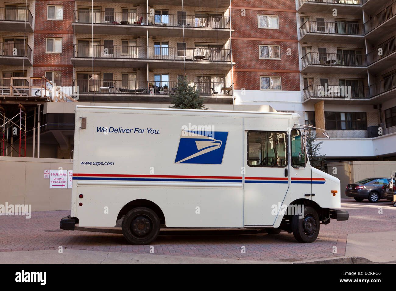 USPS delivery truck parked in front of apartment building - Arlington, Virginia USA - Stock Image