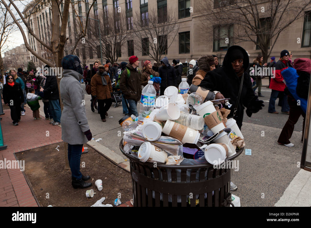 Discarded coffee cups overflowing from public trash bin - Stock Image