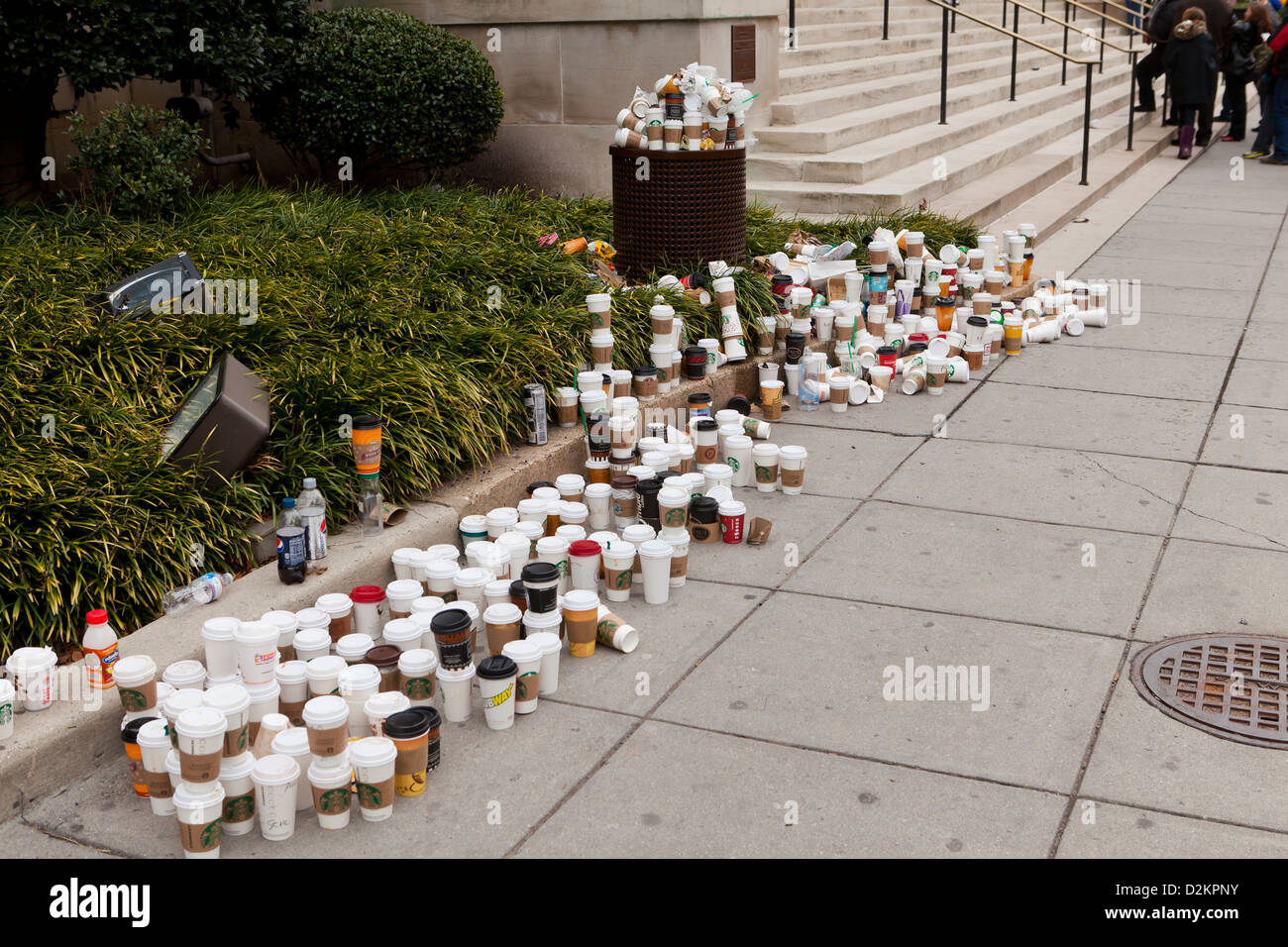 Discarded coffee cups overflowing from trash bin on public street - Stock Image