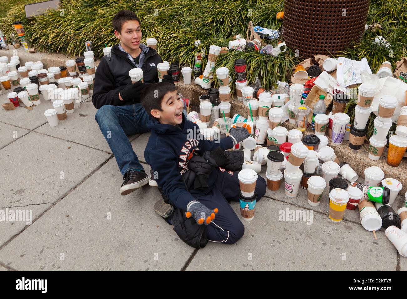 Large pile of discarded coffee cups on public sidewalk - Stock Image