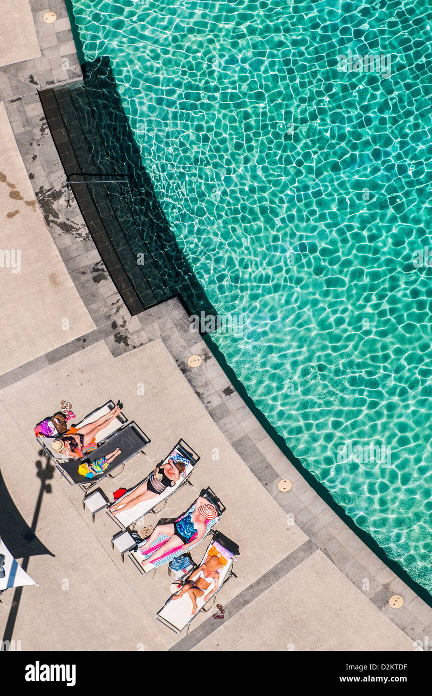 Sunbathers by the pool at Q1, Surfers Paradise, Gold Coast, Queensland, Australia - Stock Image