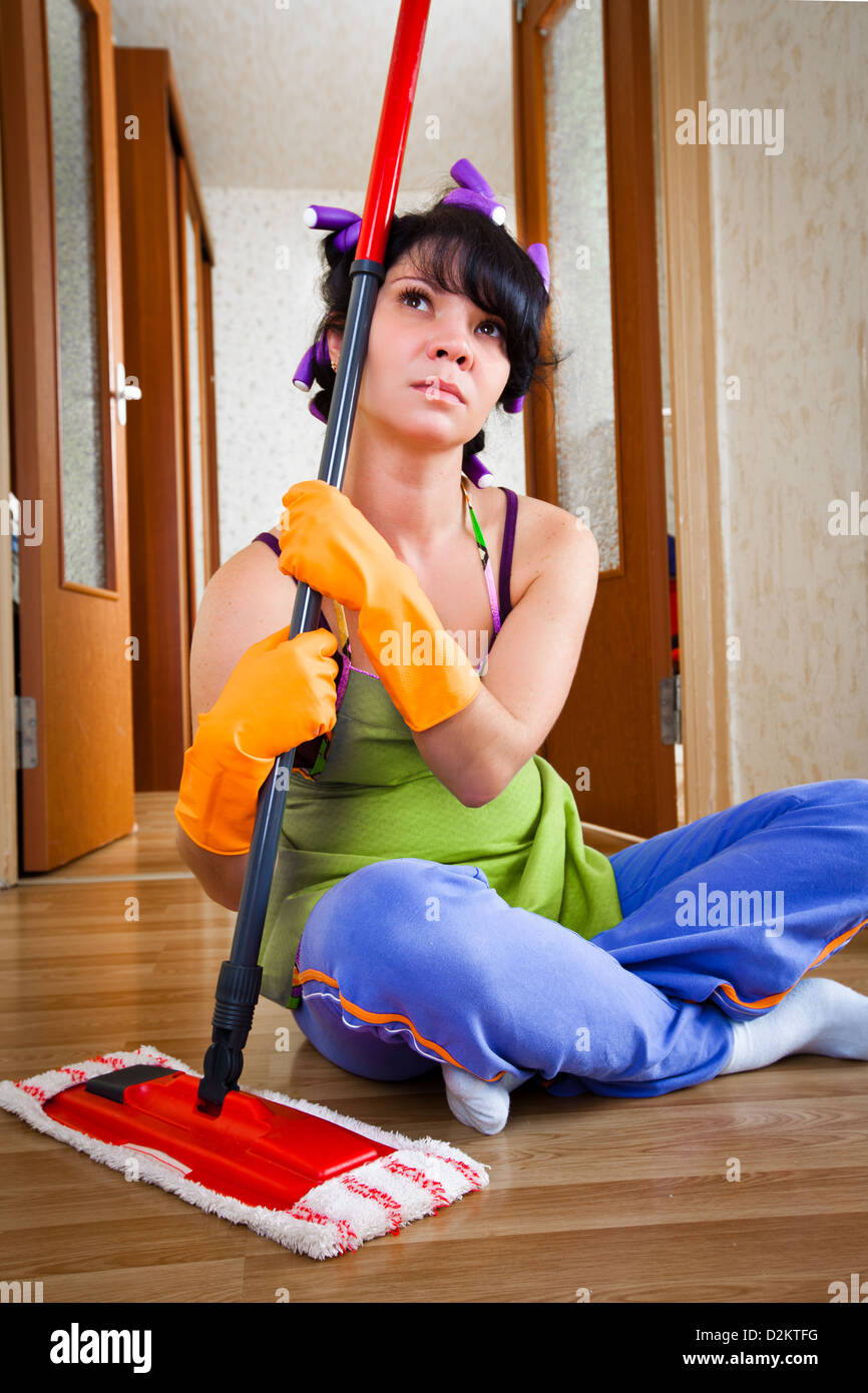 housewife sits on a floor with a mop Stock Photo