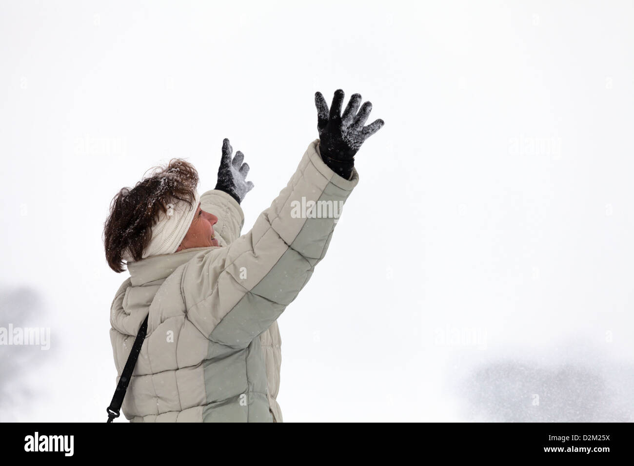 Ecstatic happy middle aged woman enjoying winter outdoors. - Stock Image