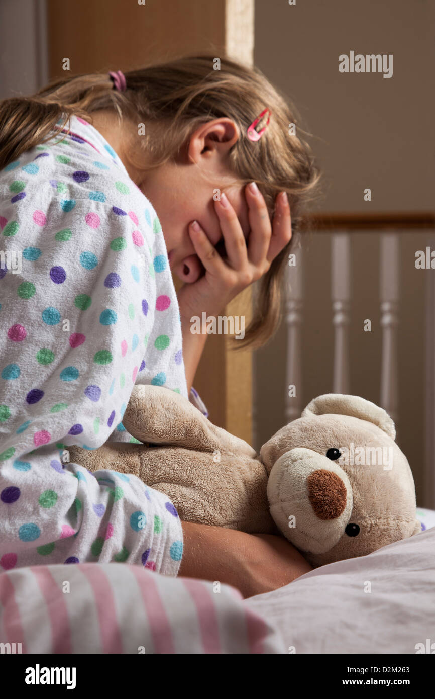 Young female wearing a pajamas clutching her teddy bear, hand covering her face. Stock Photo