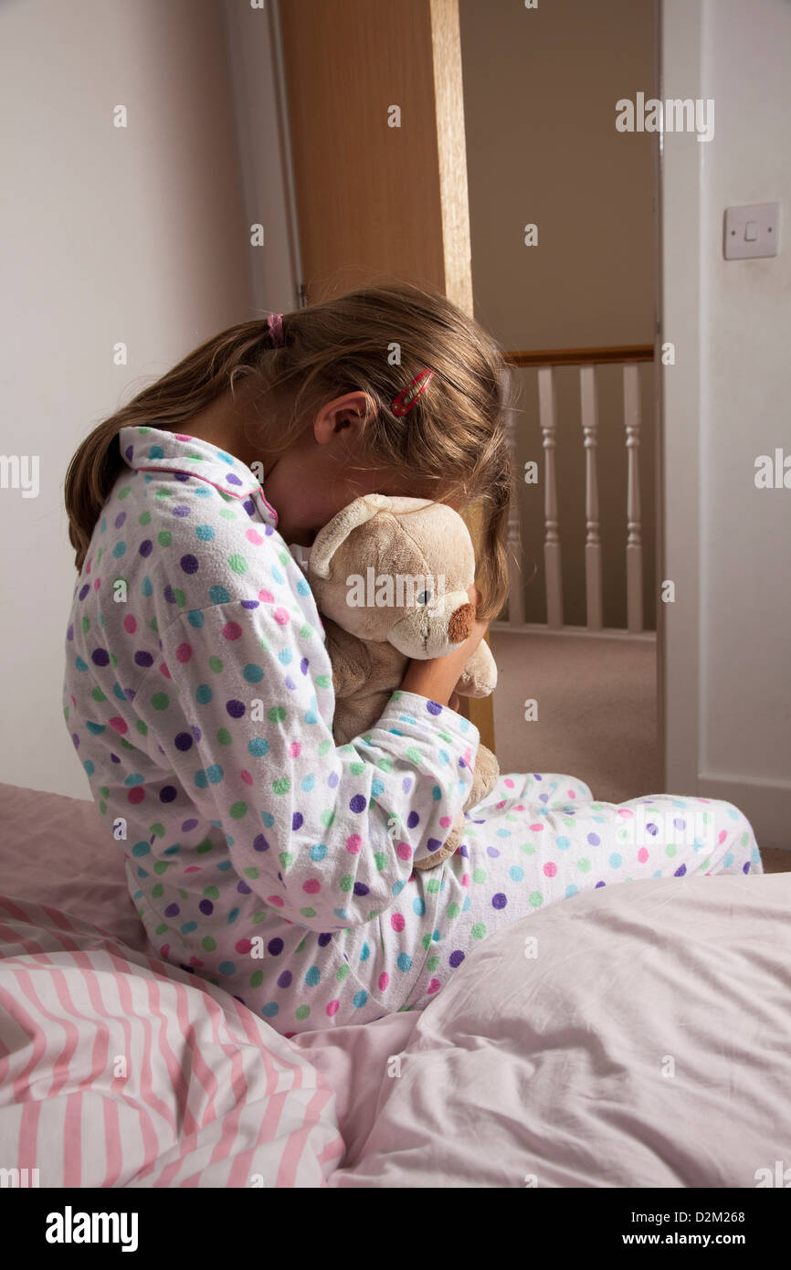 Young female wearing a pajamas clutching her teddy bear. Stock Photo