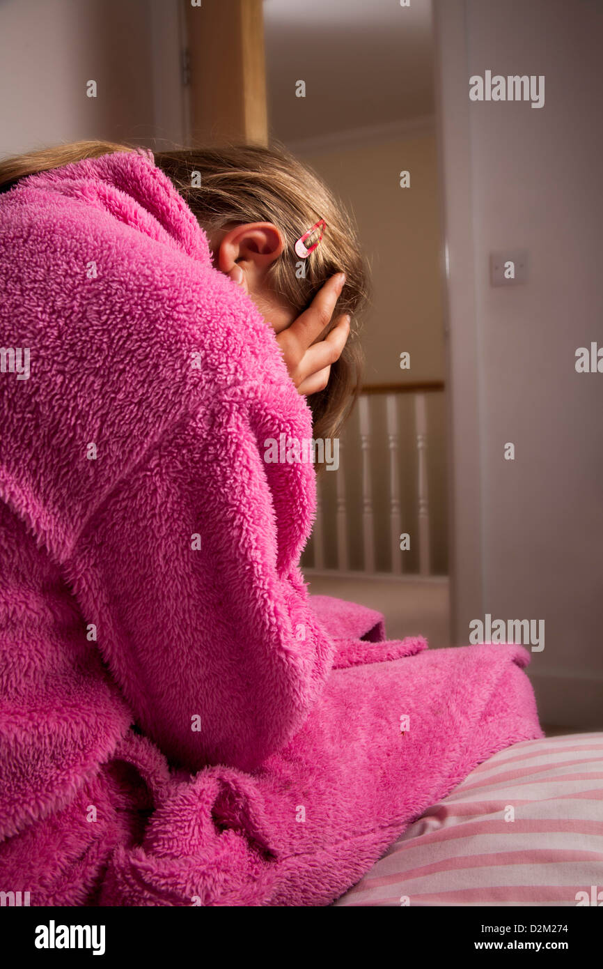 Back view of a young female wearing a pink dressing gown with her head in hands. Stock Photo