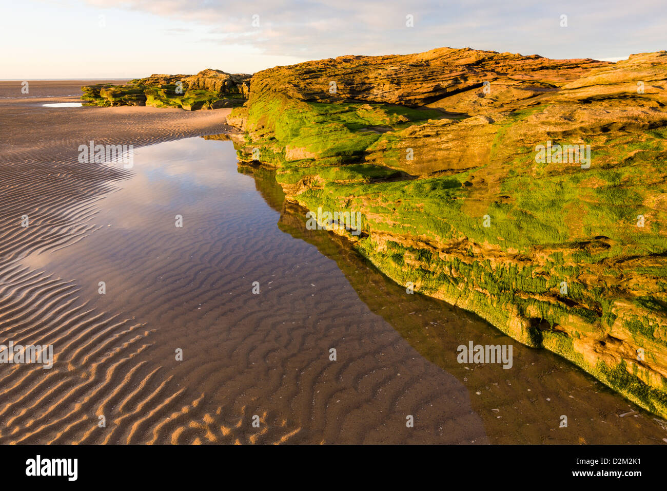 Rippled sand and sandstone rocks at low tide, Wirral, England - Stock Image