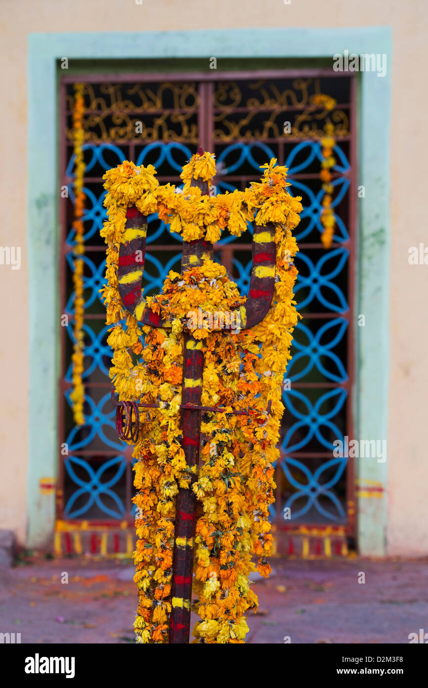 Decorative flower garlanded trident in front of a hindu temple. Andhra Pradesh, India - Stock Image