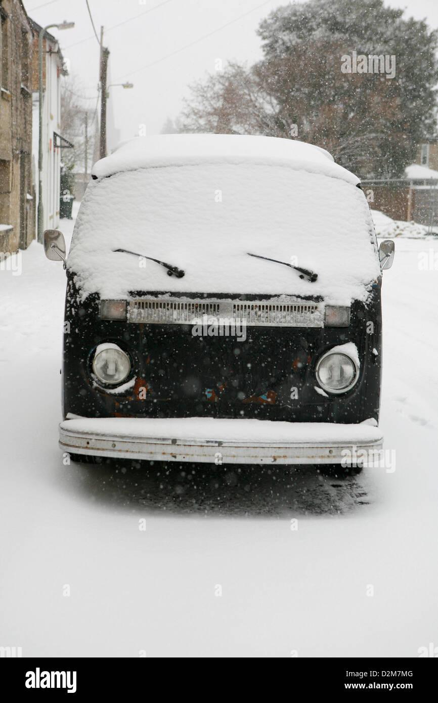 Old, retro classic Volkswagen (VW ) camper van Type 2 (T2) dark blue in colour covered in snow. - Stock Image