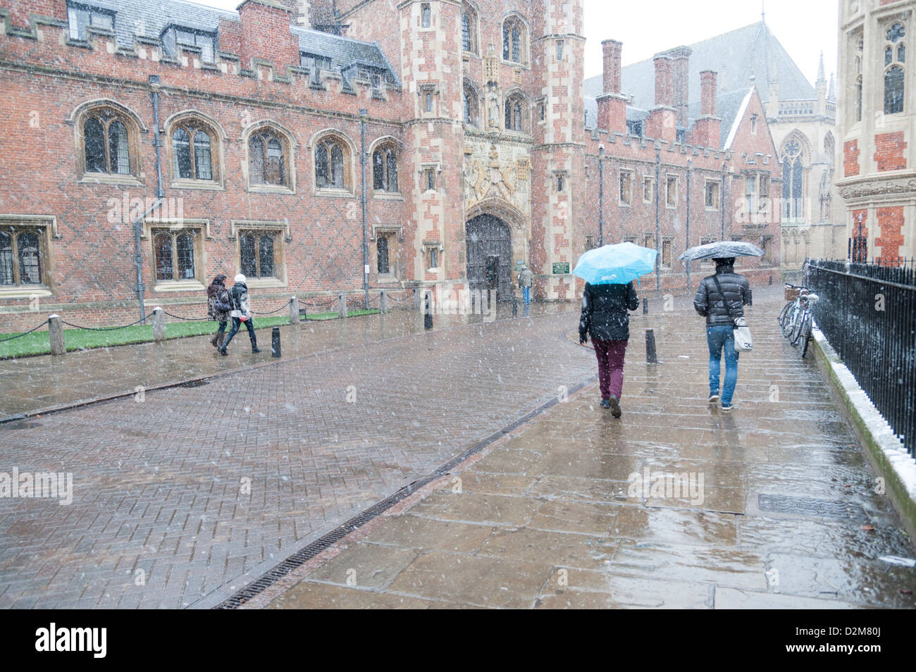 People walking in snowy bad weather in St John's Street Cambridge UK carrying umbrellas near St John's College - Stock Image