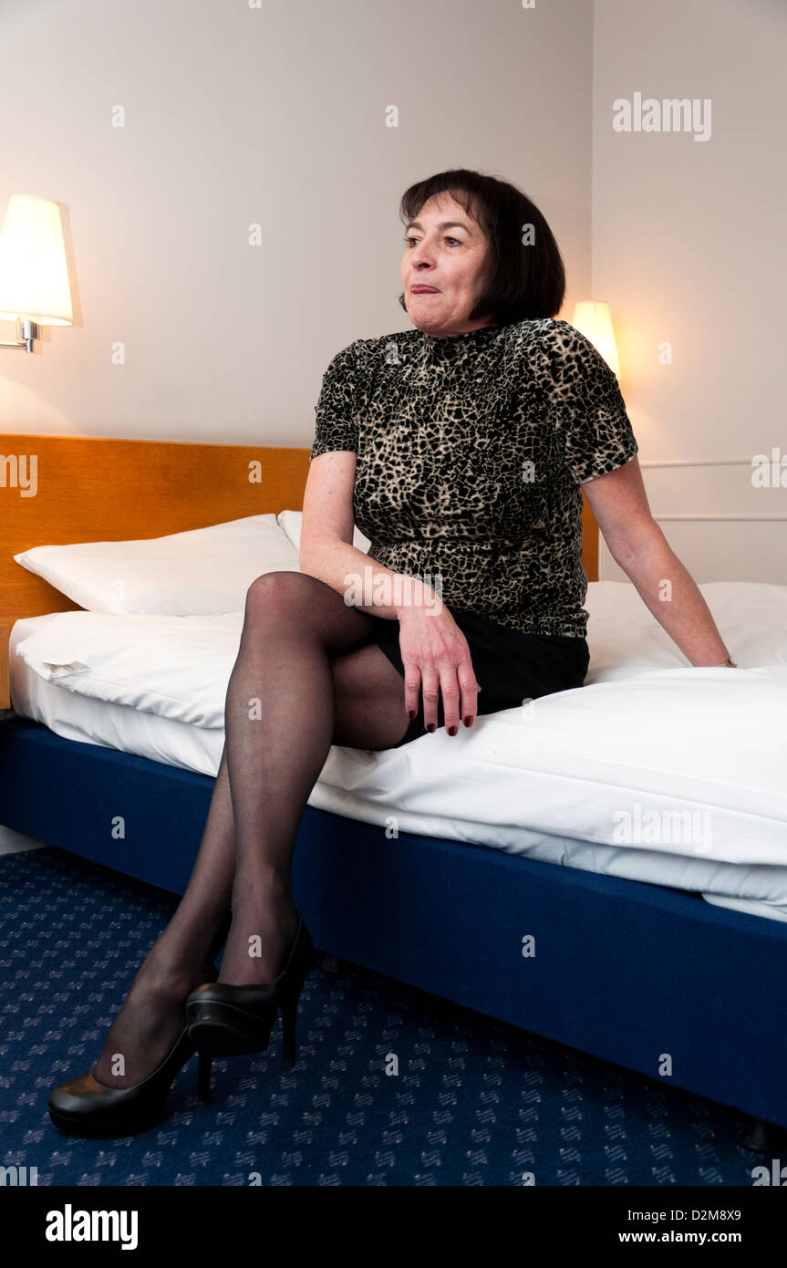 older woman sitting on hotel bed stock photo: 53306465 - alamy