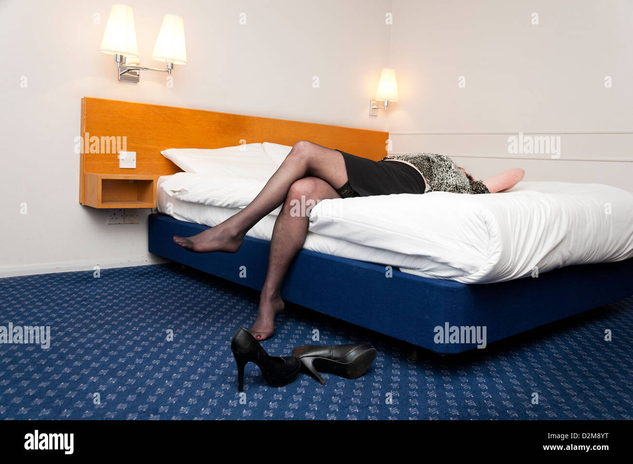 Older woman laying back on bed in hotel room. - Stock Image