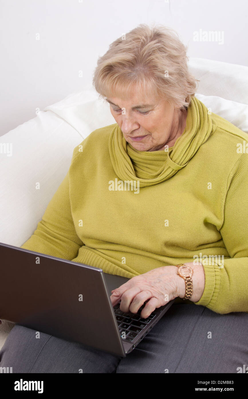 Mature lady using a laptop. - Stock Image