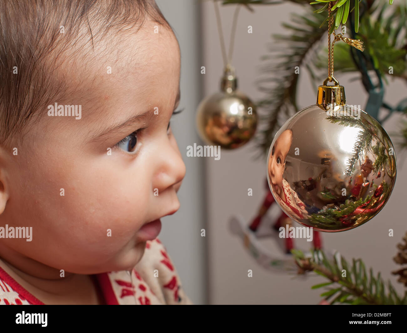 6 month old baby looking at reflection in christmas bauble stock image - What To Get A 6 Month Old For Christmas