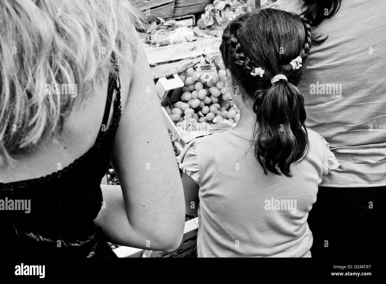 Women and a girl looking at fruit in Ballarò market, Palermo, Sicily - Stock Image
