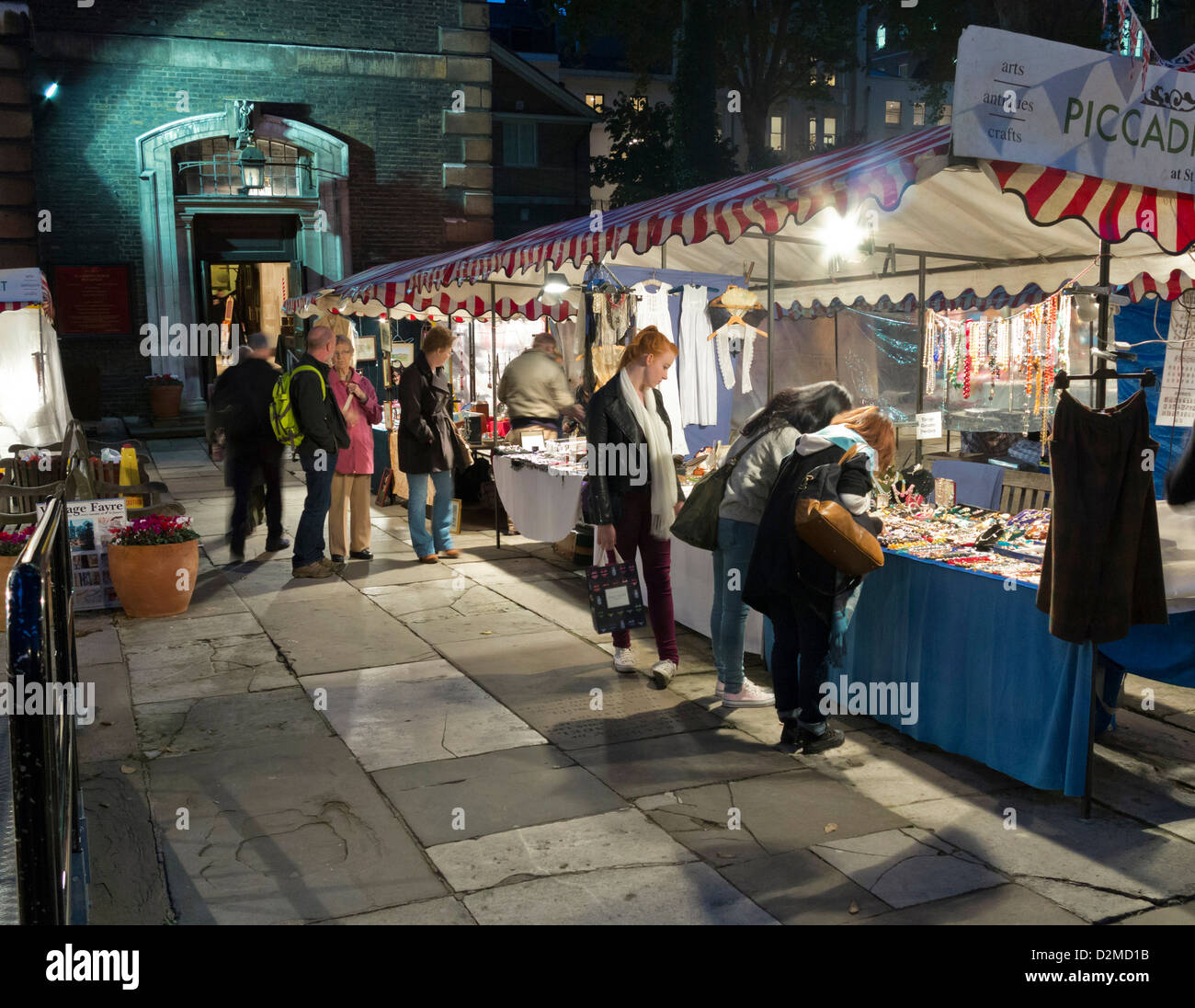 People browsing at stalls in Piccadilly Market in the grounds of St James's Church, London at night - Stock Image