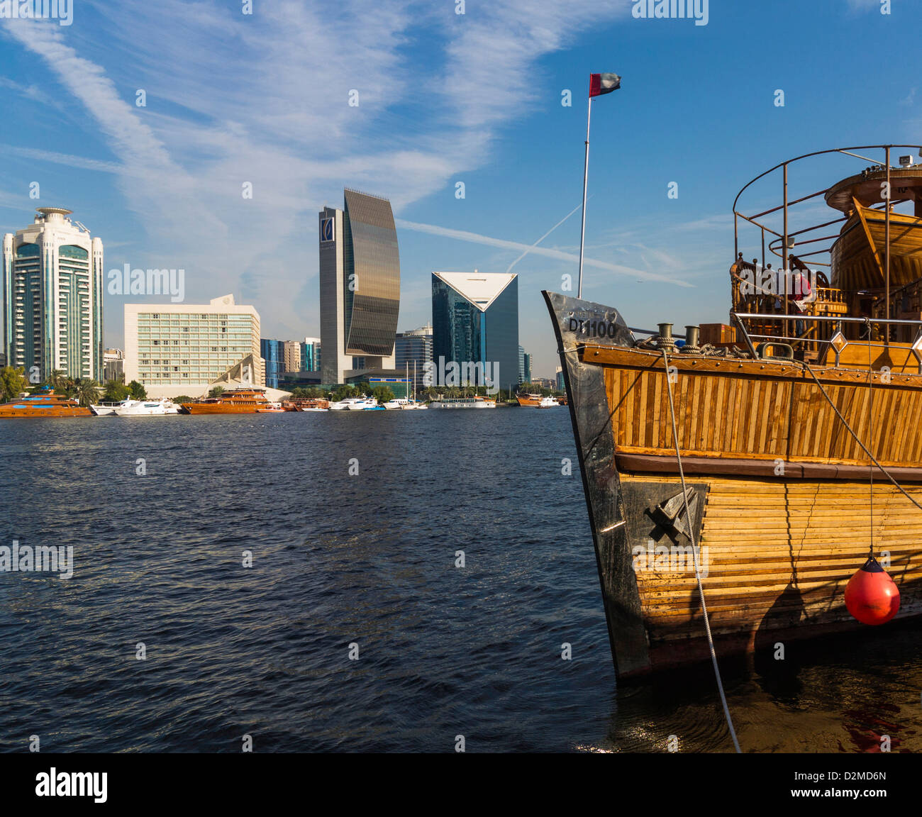 Dubai Creek with new buildings inc Bank of Dubai and Chamber of Commerce (on right) with a Dhow boat in foreground. - Stock Image
