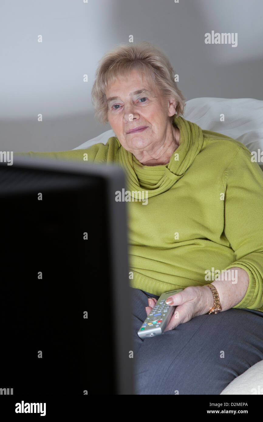 Mature lady sitting holding the remote control, watching TV. - Stock Image