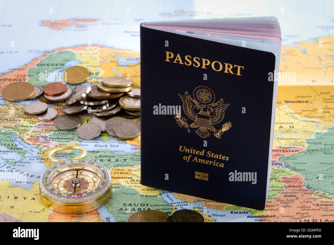 USA passport, compass and foreign coins sit on a map of Europe for an international travel concept. - Stock Image