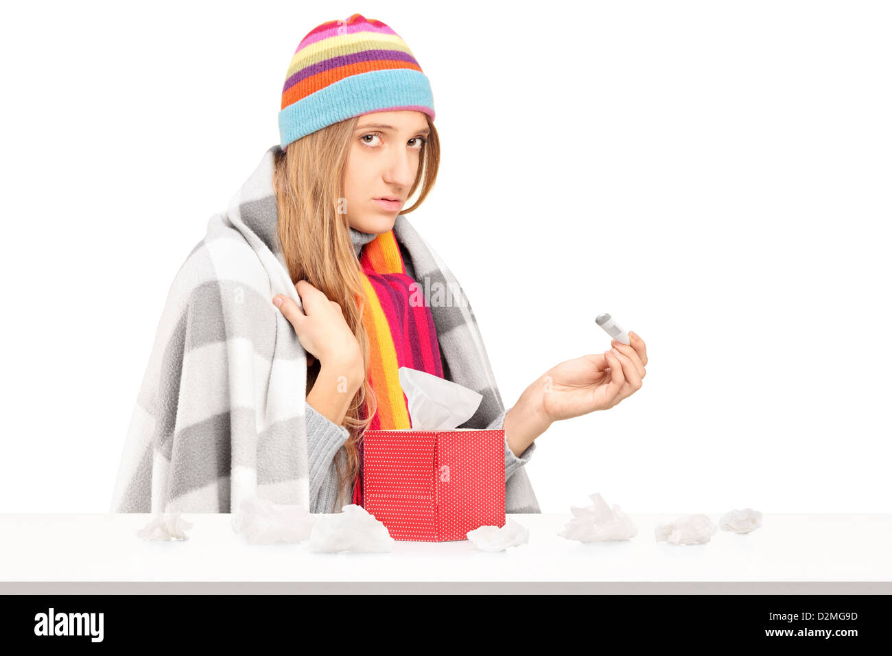 Young woman with flu holding a thermometer, box with paper tissues on a table isolated on white background - Stock Image