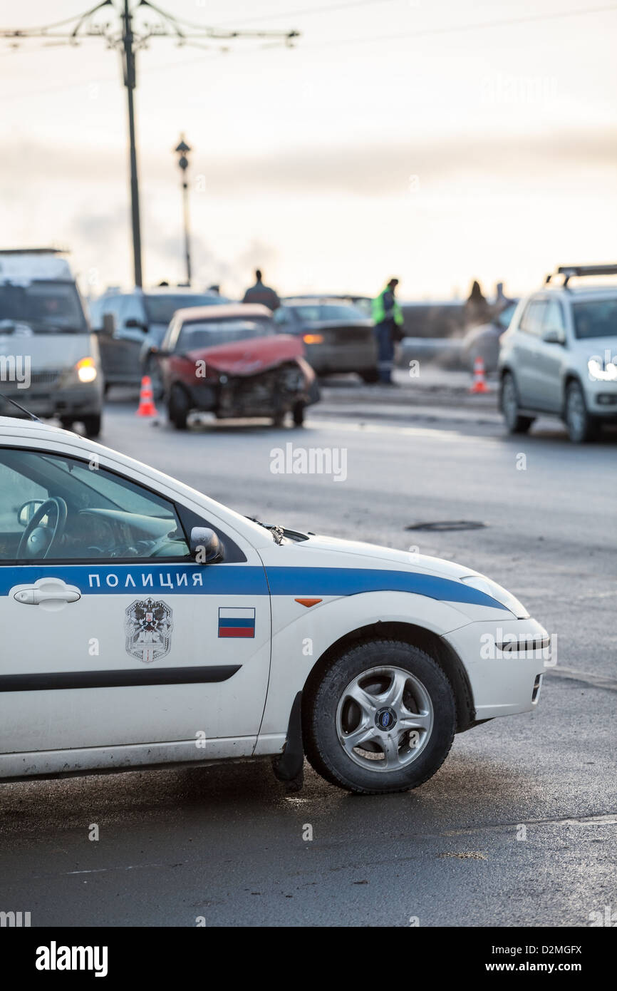 Russian police car is at the accident site with crashed car on background in St. Petersburg, Russia. Frontal impact. - Stock Image