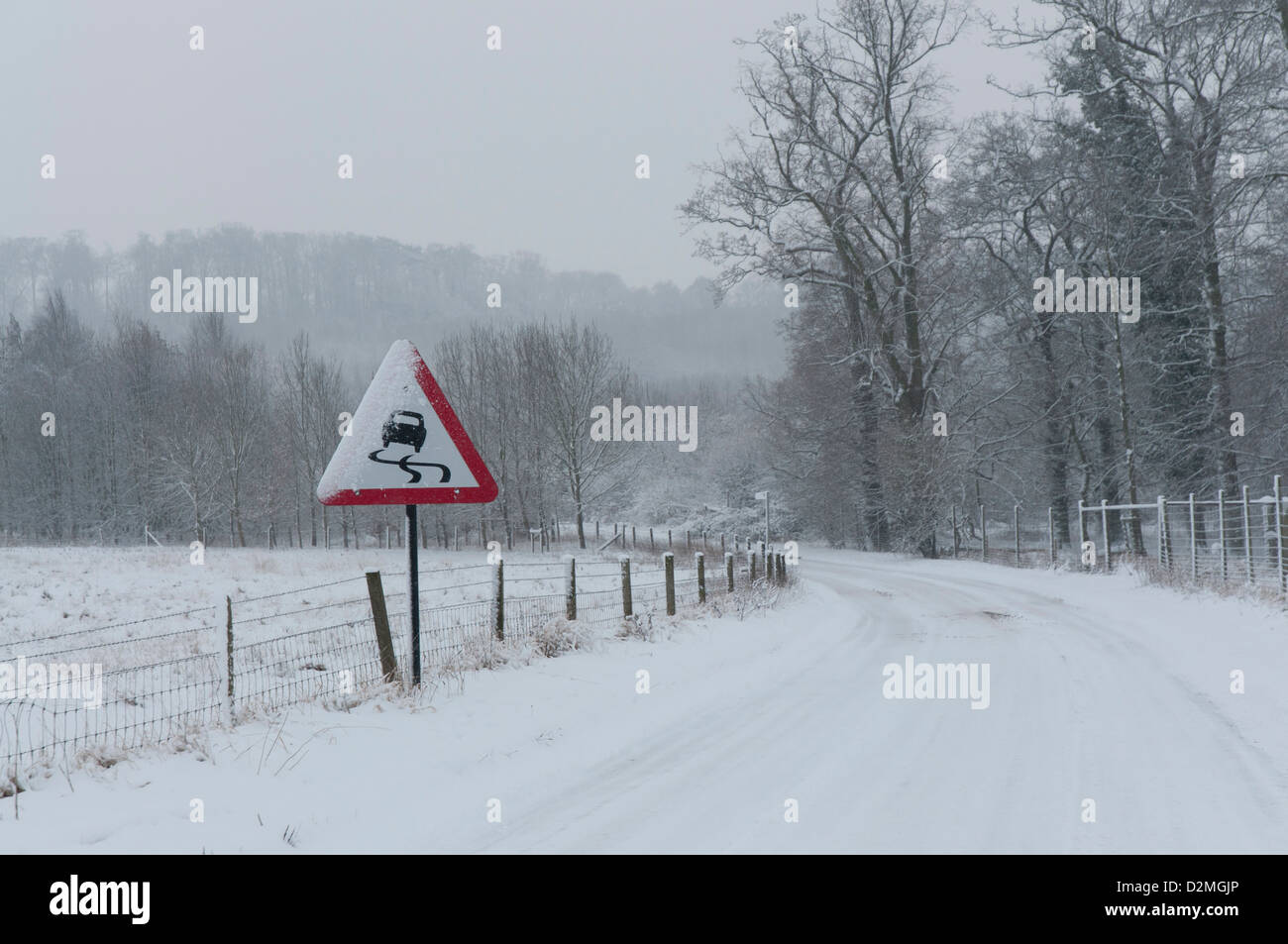 Snow covered winding country road with slippery road warning sign - Stock Image