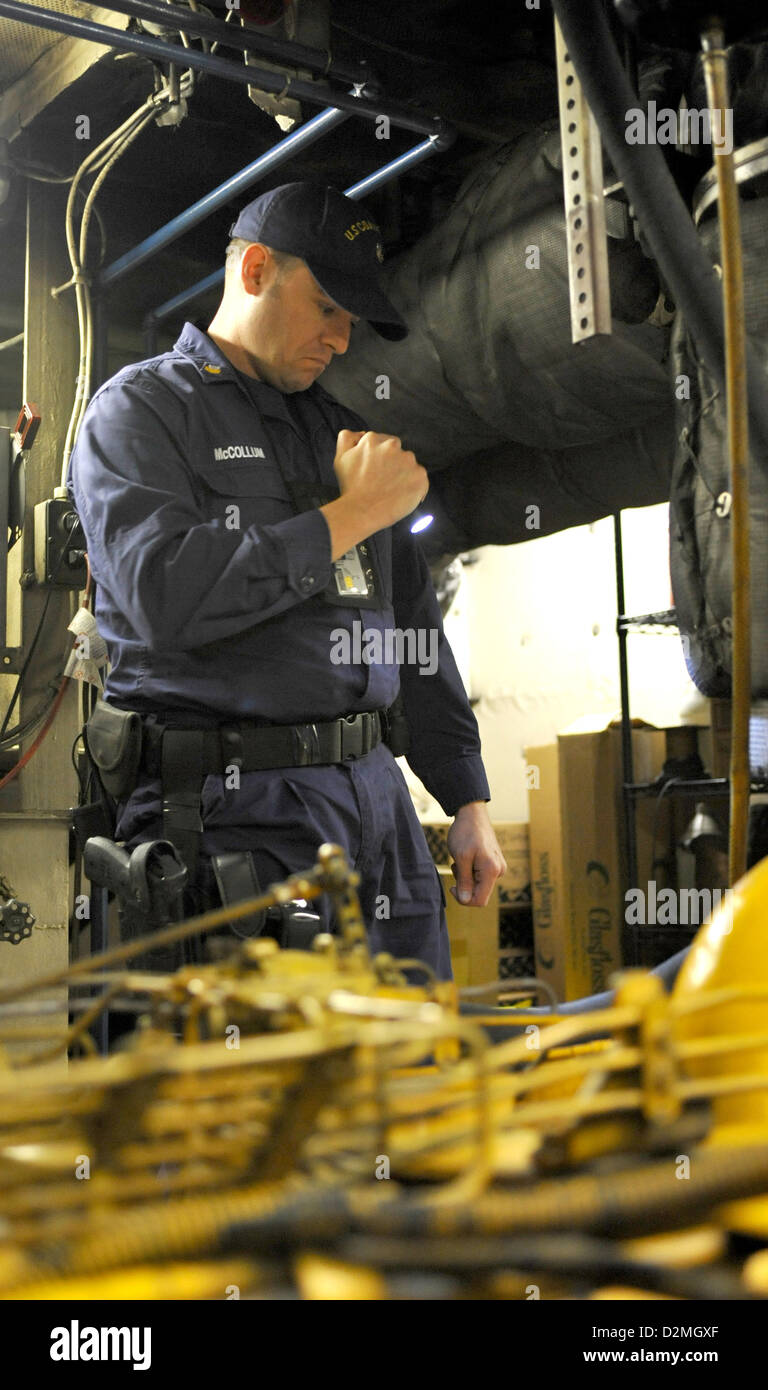 Petty officer 1st Class Thomas McCollum, a member of the Sector Baltimore Vessel Boarding and Security Team, peers - Stock Image