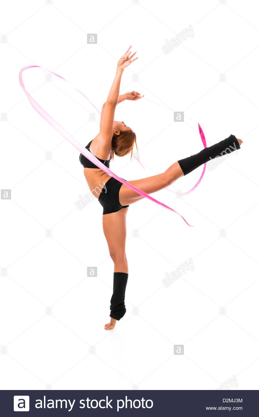 Professional gymnast woman dancer posing with ribbon over white background. - Stock Image