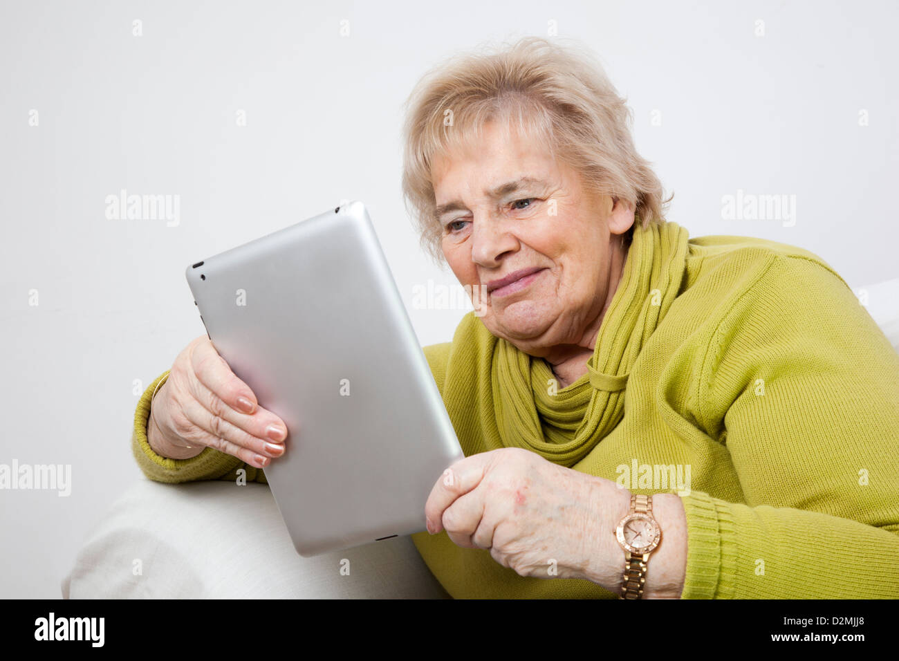 Mature lady using a digital tablet. - Stock Image