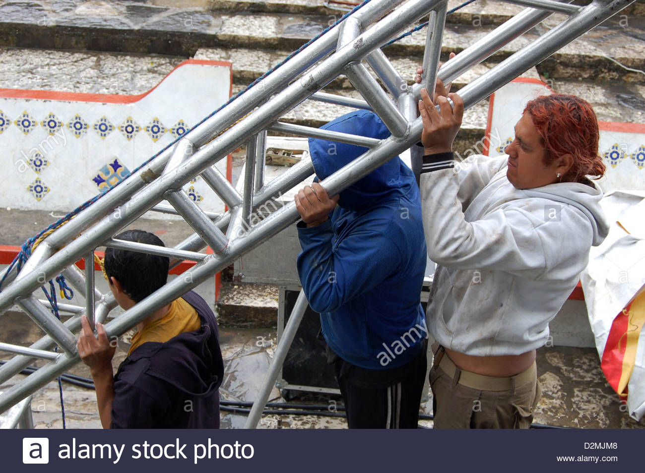 Closeup shot group of Mexican men roadies setting up scaffolding for outdoor concert in the rain. - Stock Image