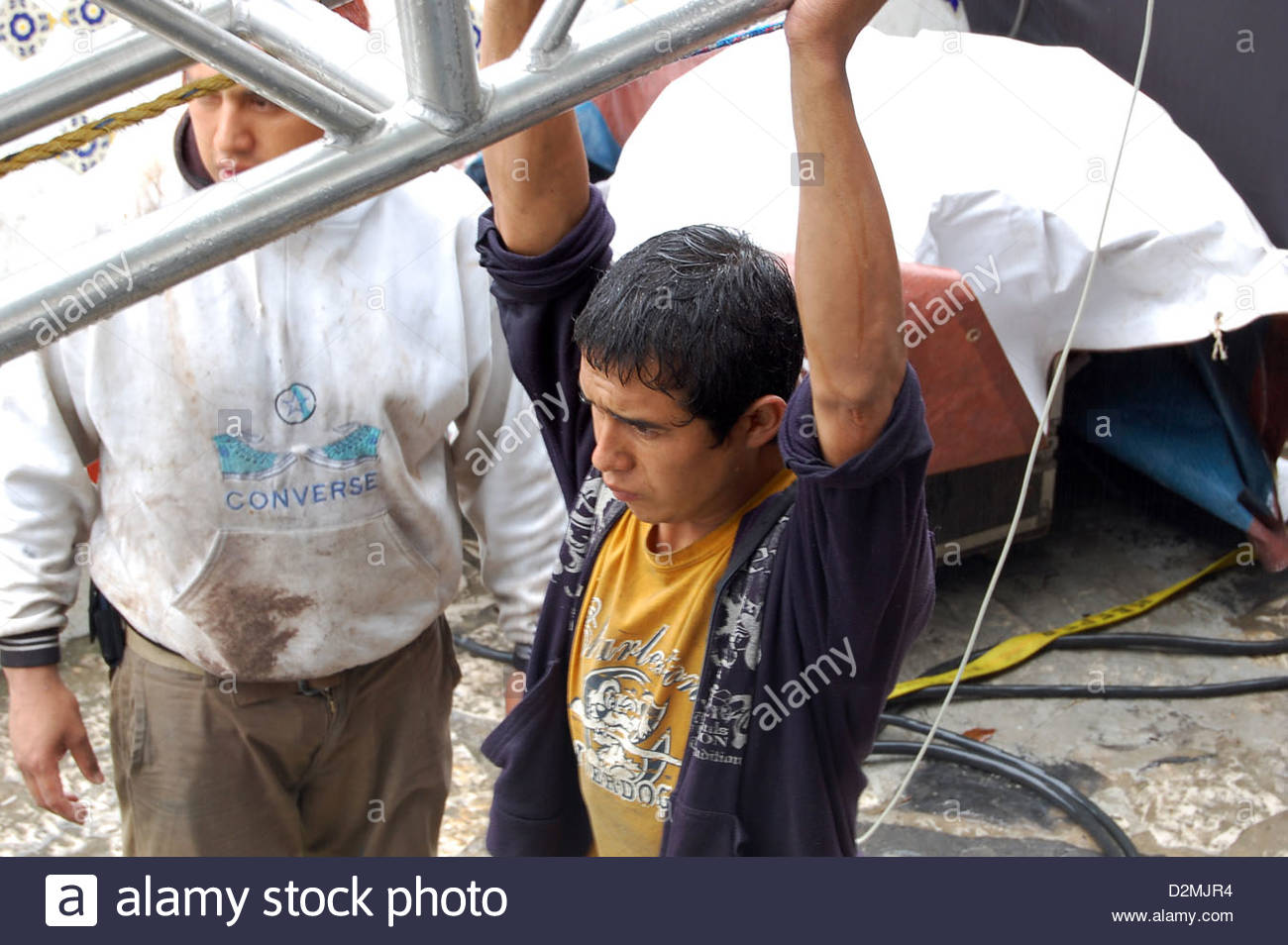 Closeup shot Mexican male roadie stage worker hoisting lifting section of scaffolding staging overhead. - Stock Image