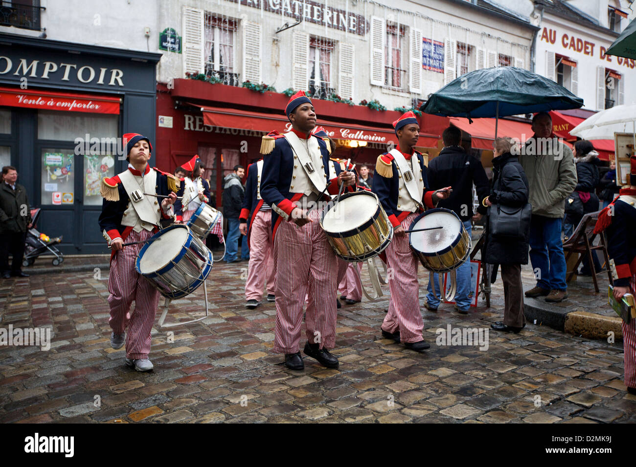 Young men march with drums in traditional costumes during a performance in the square on top of Montmartre, in Paris, Stock Photo