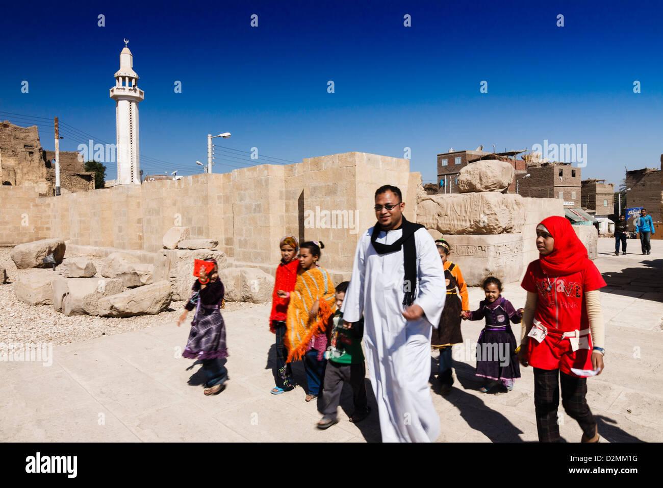 Egyptian teacher guiding a group of schoolchildren into the Abydos temple. Egypt - Stock Image