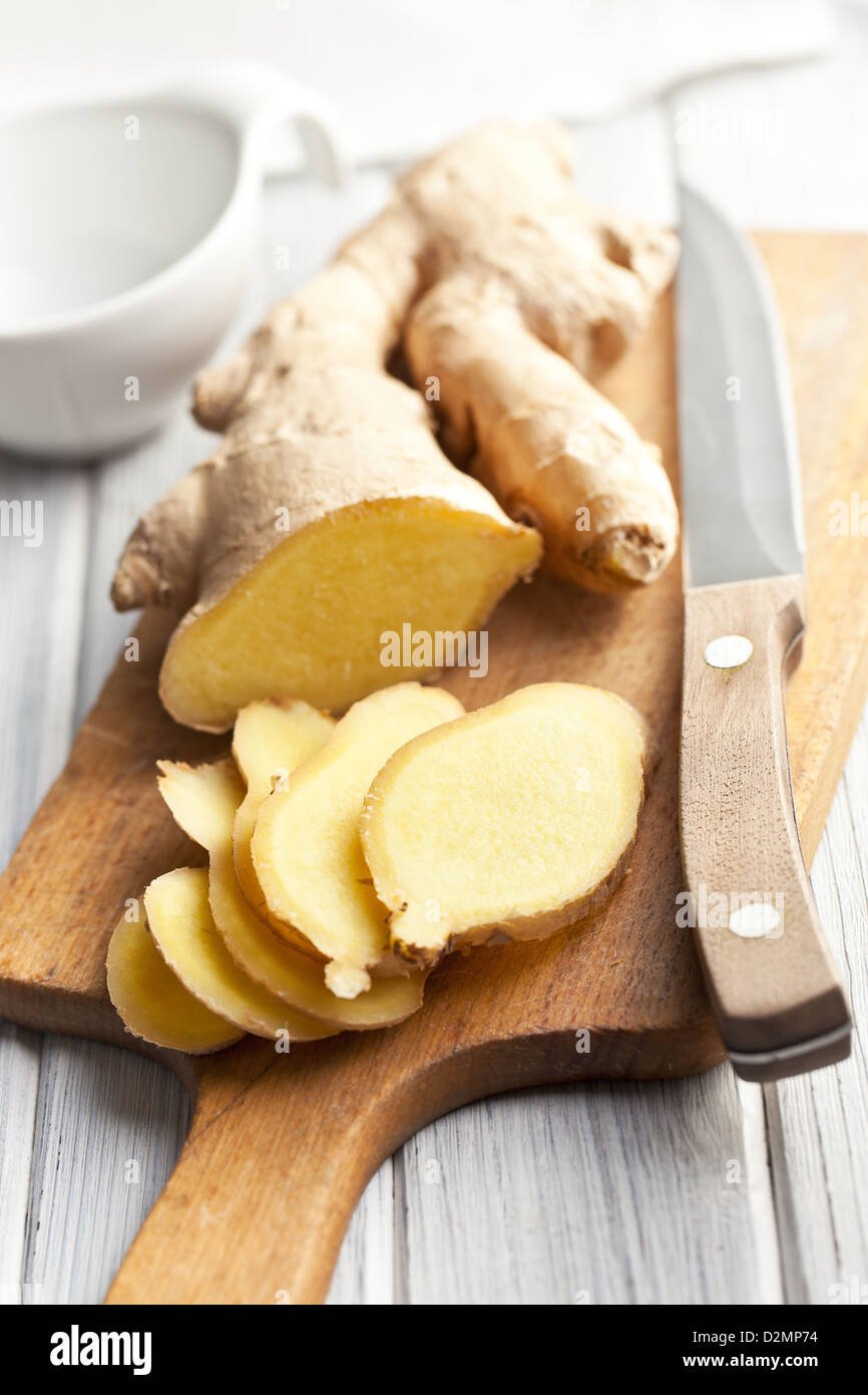 sliced ginger root on kitchen table - Stock Image