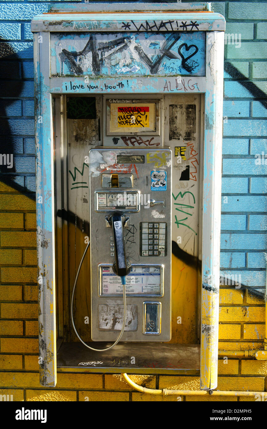Old coin-operated pay telephone on a colourful wall, Main Street, Vancouver, BC, Canada - Stock Image