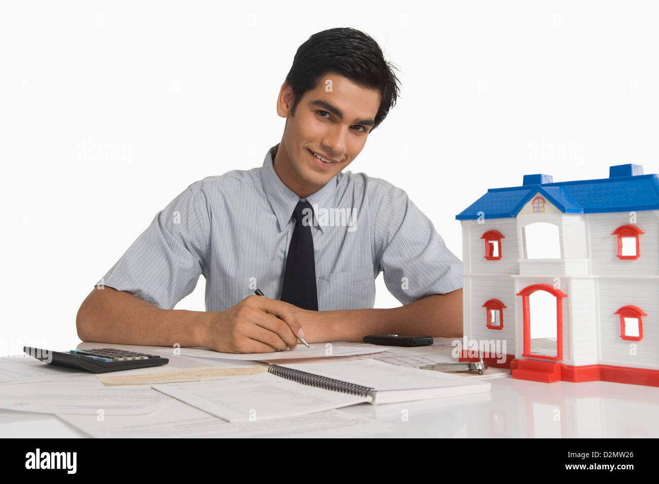 Real estate agent budgeting near a model home - Stock Image